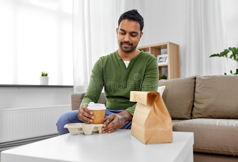 Indian man with takeaway coffee and food at home. Consumption and people concept - smiling indian man with takeaway coffee and food at home stock photography