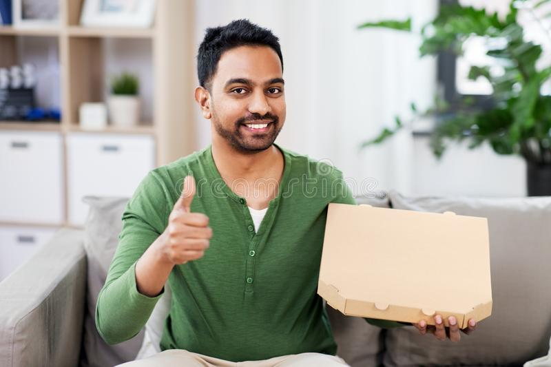 Indian man with takeaway pizza showing thumbs up. Food delivery, consumption and people concept - smiling indian man with box of takeaway pizza showing thumbs up stock image