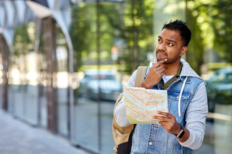 Indian man traveling with backpack and map in city. Travel, tourism and backpacking concept - indian man traveling with backpack and map in city searching stock photography