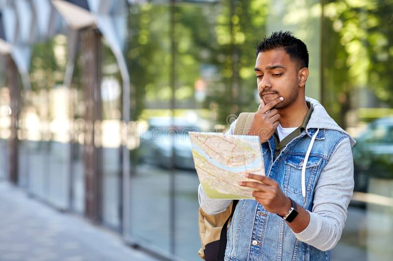 Indian man traveling with backpack and map in city. Travel, tourism and backpacking concept - indian man traveling with backpack and map in city searching royalty free stock photography
