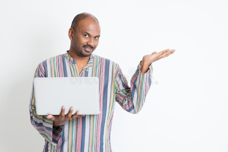 Indian man using computer and showing something. Portrait of mature casual business Indian man using laptop computer, hand showing something, standing on plain royalty free stock photos