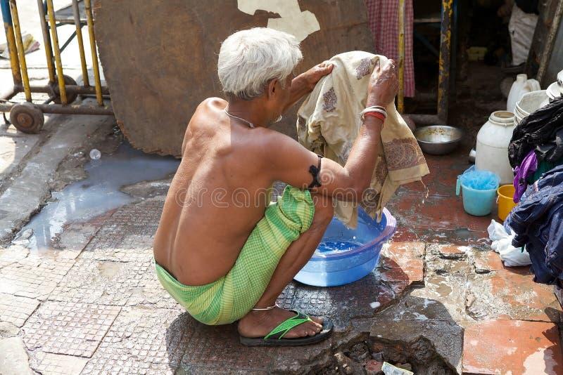 Indian man is washing some clothes, Kolkata, India royalty free stock image