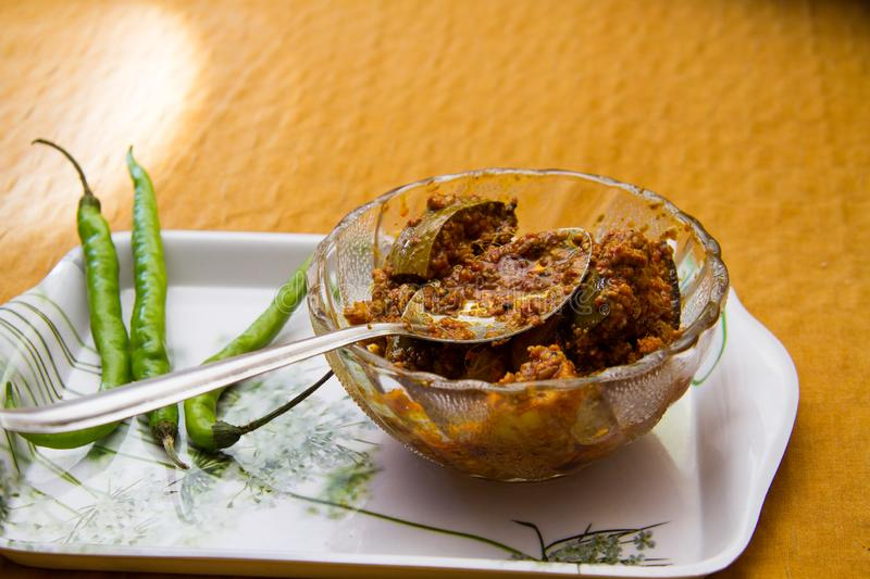 Indian Mango Pickle in bowl with green chillies royalty free stock photography