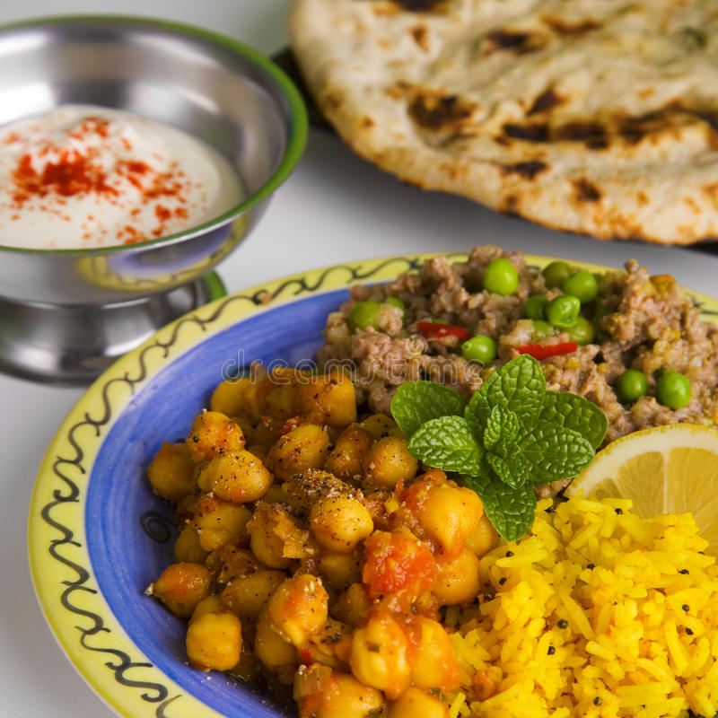 Indian Meal. Of keema matar, masala channa, lemon rice, naan bread and yoghourt, which is minced lamb with peas, spicy chickpeas, yellow rice, nan bread and stock image