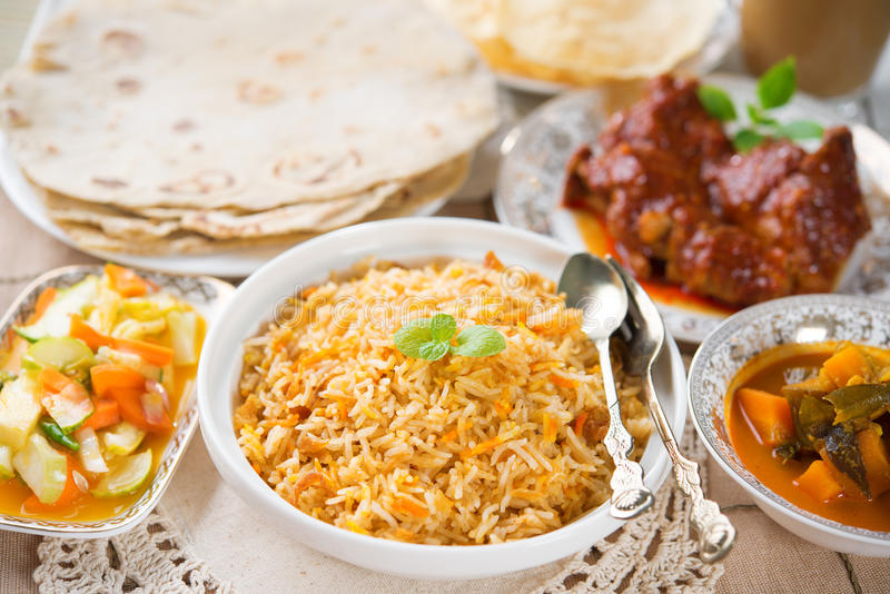 Indian meal biryani rice. Chicken curry, masala milk tea, acar vegetable, roti chapatti and papadom royalty free stock photo