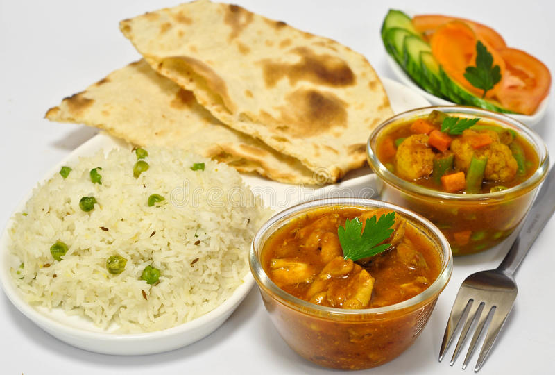 Indian Meal with Chicken curry. Indian meal consisting of chicken curry as the main dish, along with vegetable curry, Indian Bread, Rice and Salad stock photography
