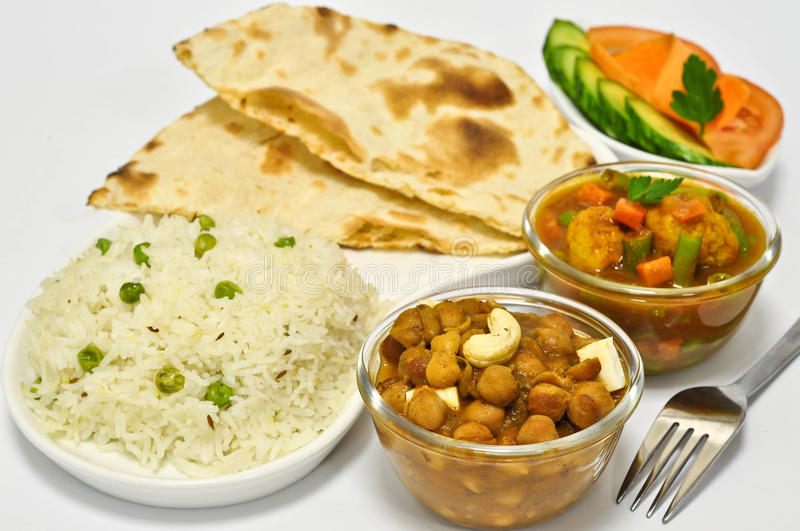 Indian Meal with Chickpeas. Indian meal consisting of chickpeas as the main dish, along with vegetable curry,Indian Bread,Rice and Salad royalty free stock photography