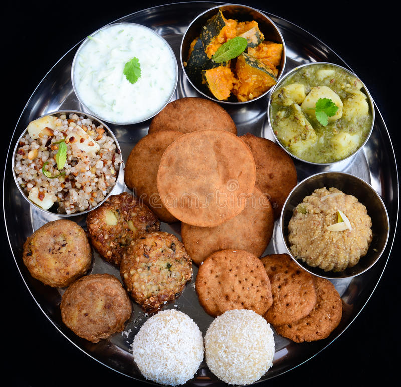 Indian meal. Consisting of potato curry,pumpkin curry,coconut laddoo sweet,fried potato balls, sabudana sago khichdi,curd raita,fried poori,sama halwa in royalty free stock photography