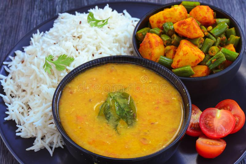 Indian meal - Mung dal lentil, rice and beans curry. Indian gluten-free vegan meal -bowl of Moong dal lentil, rice and beans curry served with salad royalty free stock images