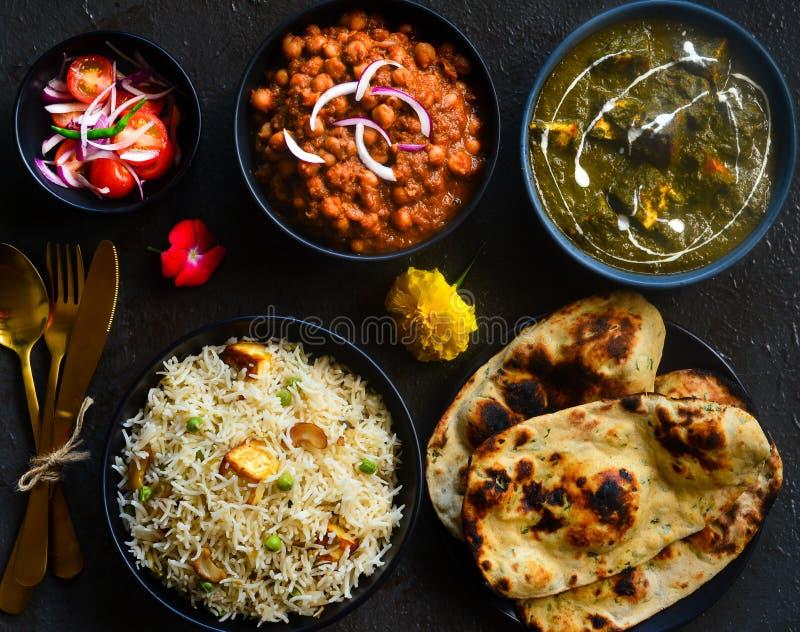 North Indian party meal-Punjabi vegetarian platter. Indian meal with palak paneer,pindi chole masala,awadhi biryani,Tandoori Roti and salad stock photo