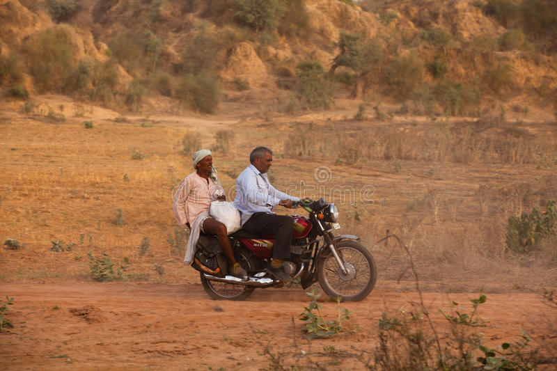 Indian men on Motorbike. Riding on dusty road near Agra, India royalty free stock photography