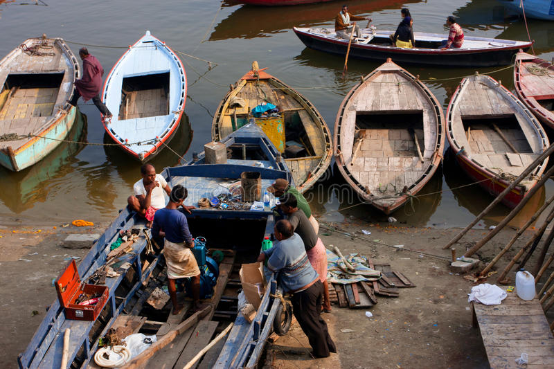 Indian men try to fix the motor of an old riverboat at the Ganges river dock royalty free stock photography