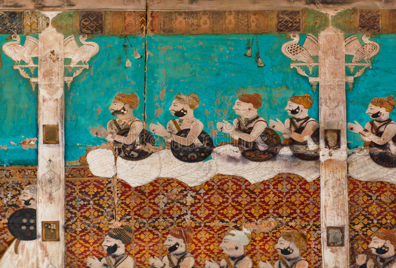 Indian men in vintage dresses sitting in a palace. Mural on the wall of Indian palace in Bundi city, Rajasthan, India royalty free stock photography