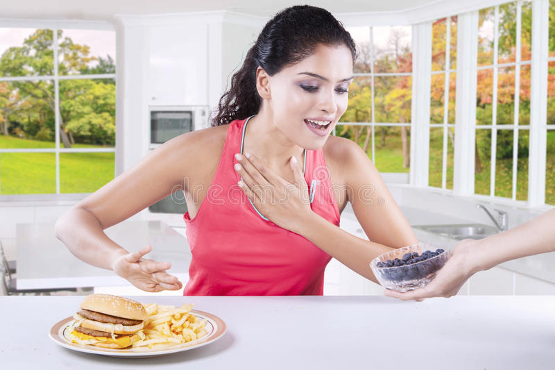Indian model choosing to eat blueberry. Photo of pretty woman choosing a bowl of blueberry and refuse hamburger in the kitchen with autumn background on the stock photo