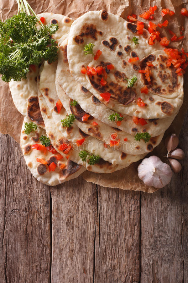 Indian Naan flat bread with garlic and herbs. vertical top view stock photography