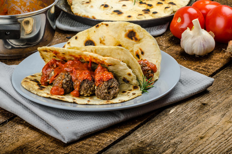 Indian naan with meatballs and tomato sauce stock images