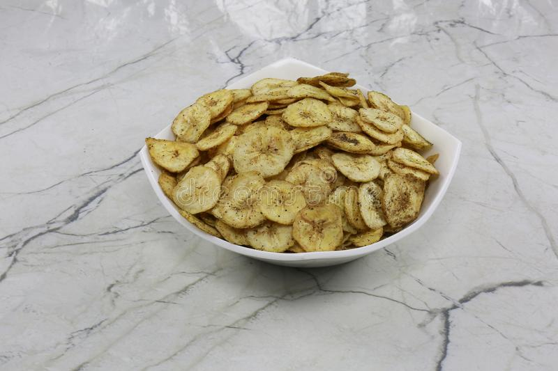 INDIAN NAMKEEN BANANA CHIPS SALTY. Indian namkeen snacks lahsun gathiya spices crunchy white bowl background flavour fried oil royalty free stock photo