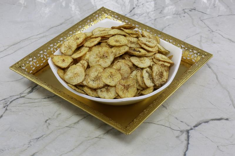 INDIAN NAMKEEN BANANA CHIPS SALTY. Indian namkeen snacks lahsun gathiya spices crunchy white bowl background flavour fried oil royalty free stock images