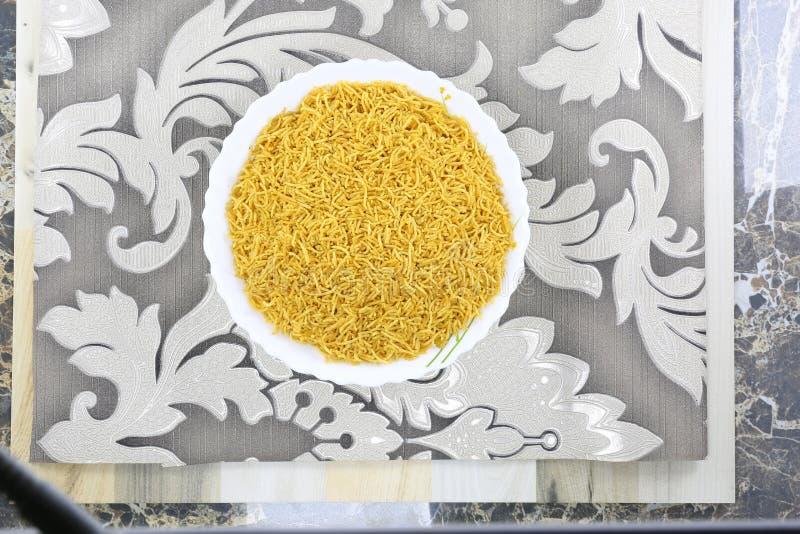 INDIAN NAMKEEN BAREEK SALTY SNACKS. Indian namkeen snacks lahsun gathiya spices crunchy white bowl background flavour fried oil stock image