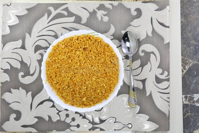 INDIAN NAMKEEN PEANTU DAL CHANA MIXTURE. Indian namkeen snacks lahsun gathiya spices crunchy white bowl background flavour fried oil royalty free stock photo