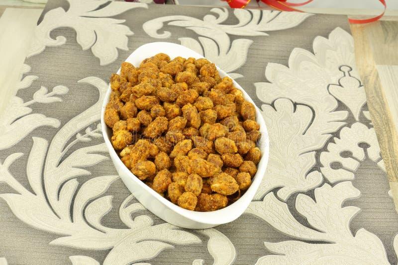 INDIAN NAMKEEN PEANUT TASTY SNACKS. Indian namkeen snacks lahsun gathiya spices crunchy white bowl background flavour fried oil stock image