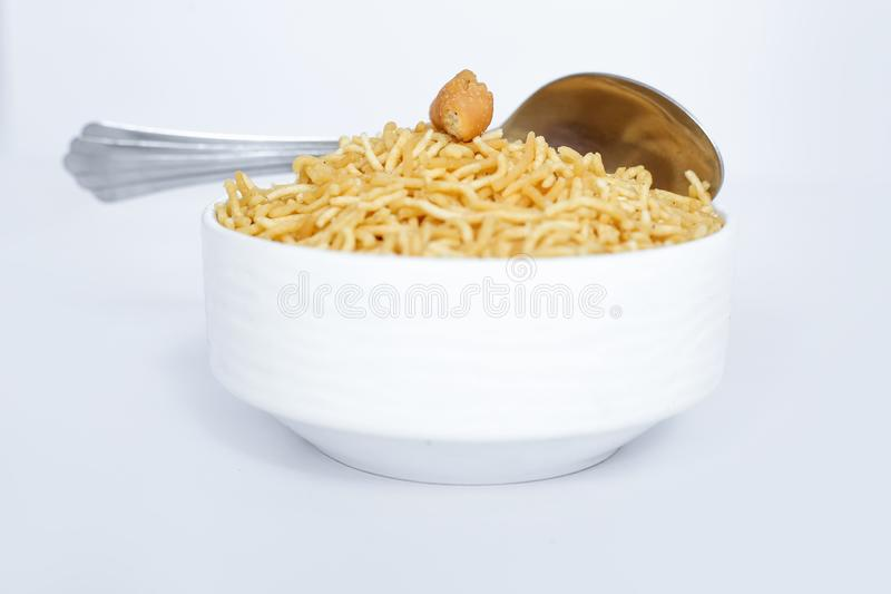 Indian namkeen snacks bikaneri bhujia with spoon in the bowl stock images