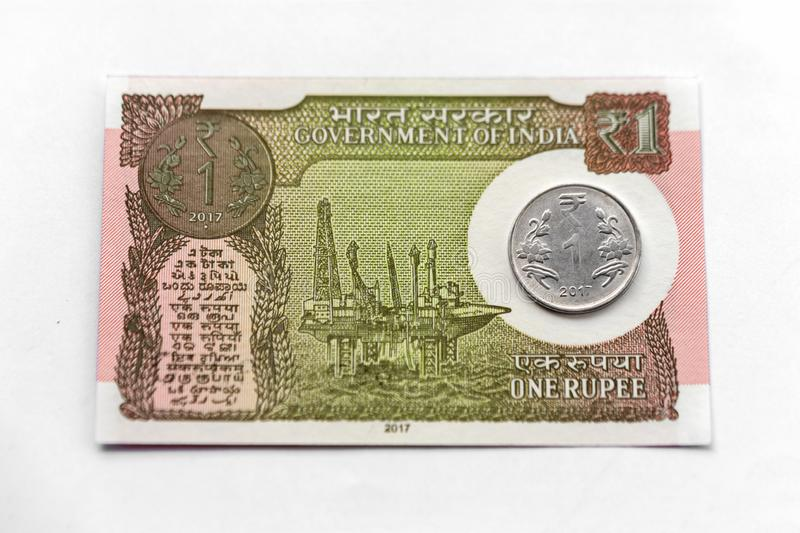 Indian New One Rupee Note & Coin. Indian brand new one rupee banknote cash money with one rupee coin on a white background stock photography