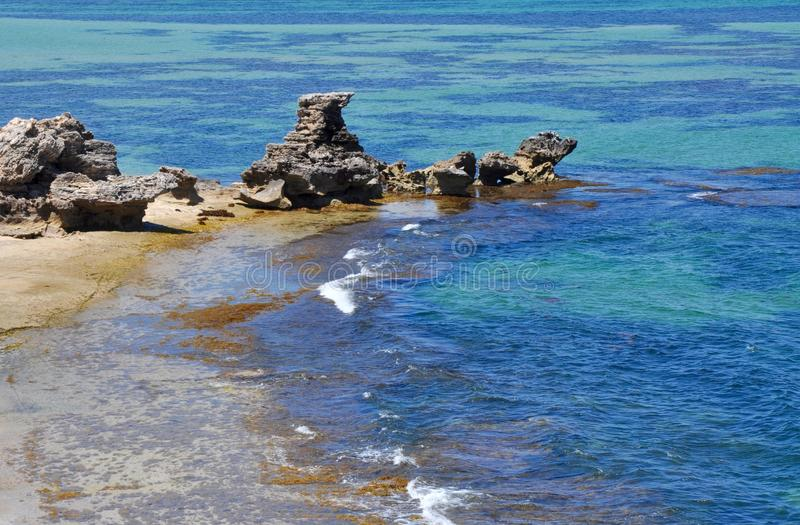 Indian Ocean Landscape with Rocky Secluded Beach. Stunning blue and turquoise Indian Ocean Waters with a sandy secluded beach spotted with limestone rock stock photos