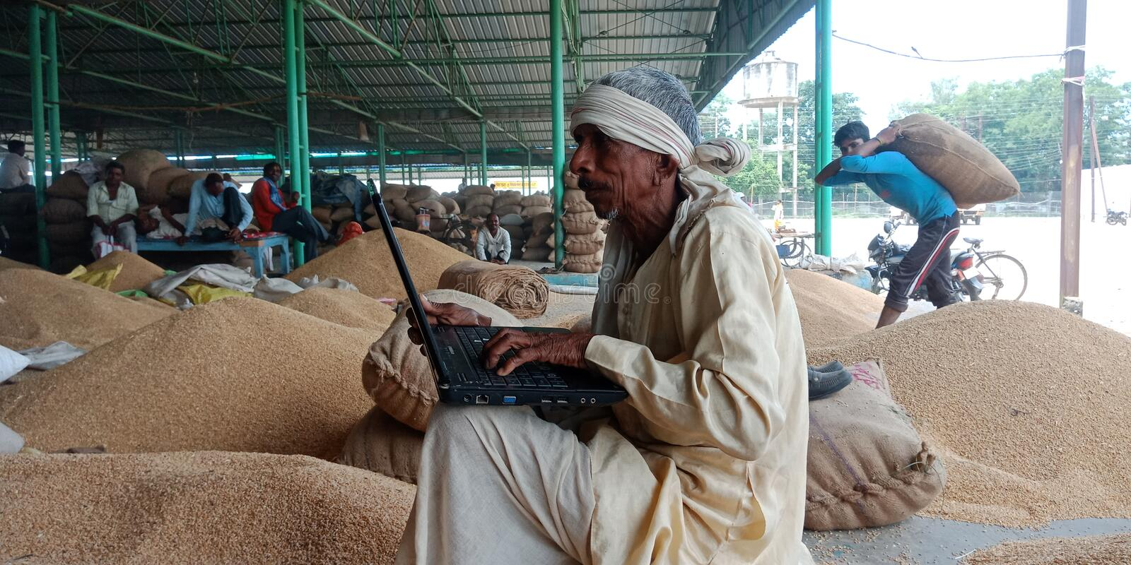An indian old man working on laptop computer system seating at agriculture field. Amazon, logo, displayed, mobile, phone, screen, online, village, area, farmer royalty free stock photos