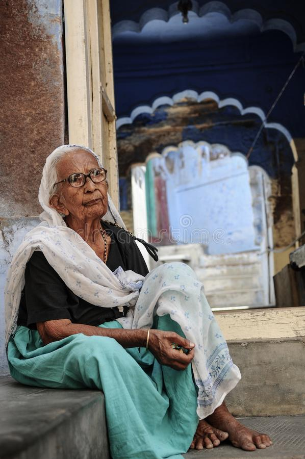 Indian old woman resting in front of her house stock images