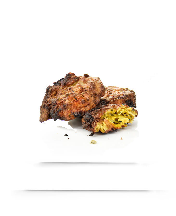 Indian Onion Bhajis. Baked traditional Indian Onion Bhajis against a white background. Sharp focus with generous accommodation for copy space. The perfect image royalty free stock image