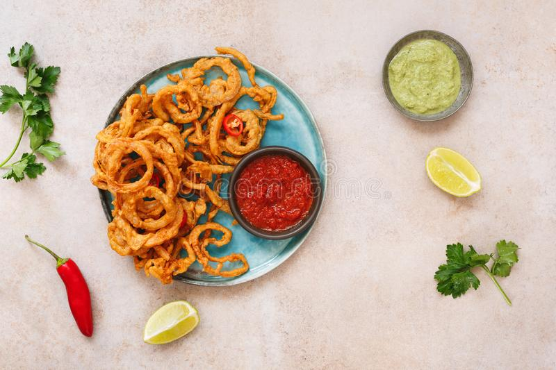 Indian onion bhajis with two sauces. Red chilli garlic and mint chutney. Top view, blank space stock photos