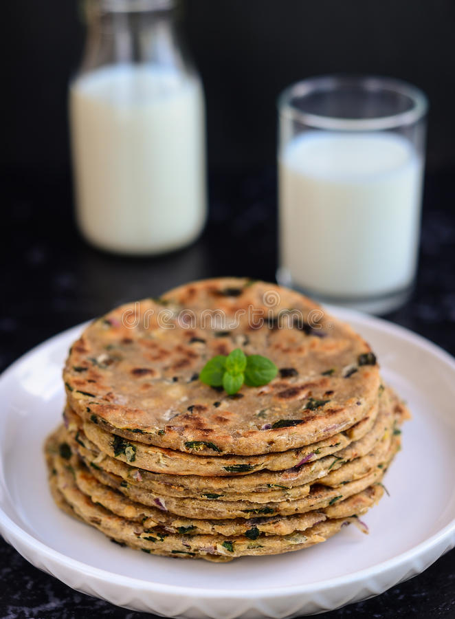 Indian Parantha (stuffed indian bread) and milk. Stack of Indian Parantha (stuffed Indian bread) a plate and milk stock image