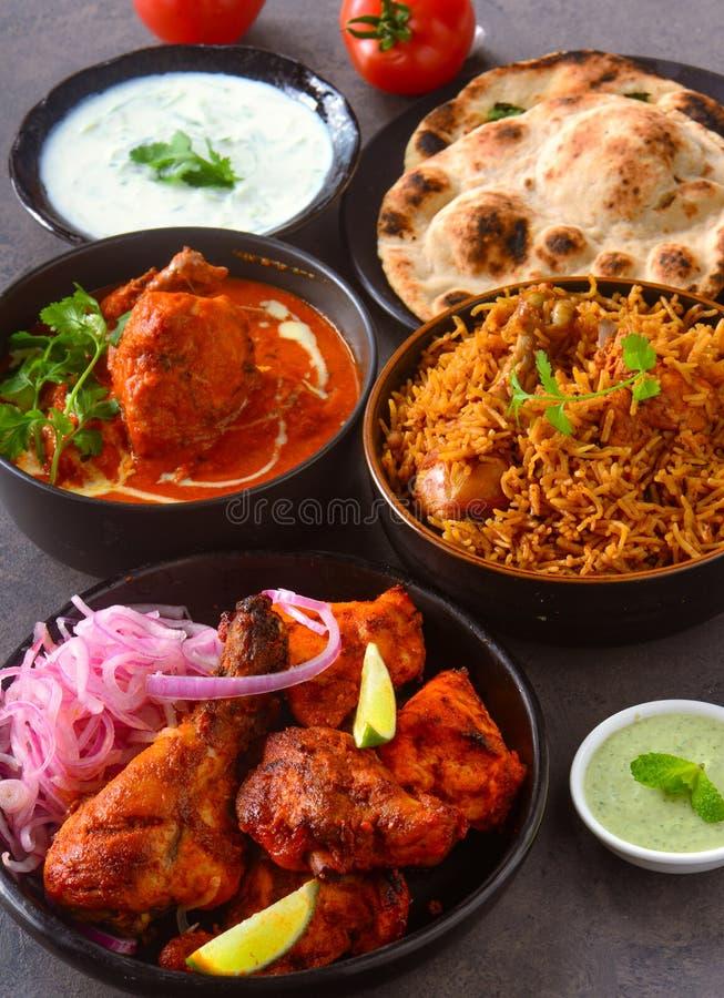 Indian chicken platter. Indian party meals served with Tandoori roti,Chicken biryani,Murg kadai,chicken tikka masala, yogurt dup raita,mint chutney and Fried royalty free stock image