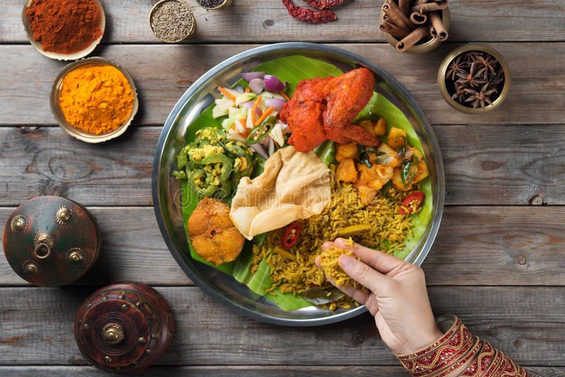 Indian people eating biryani rice. Overhead view of Indian woman's hand eating biryani rice on wooden dining table royalty free stock images