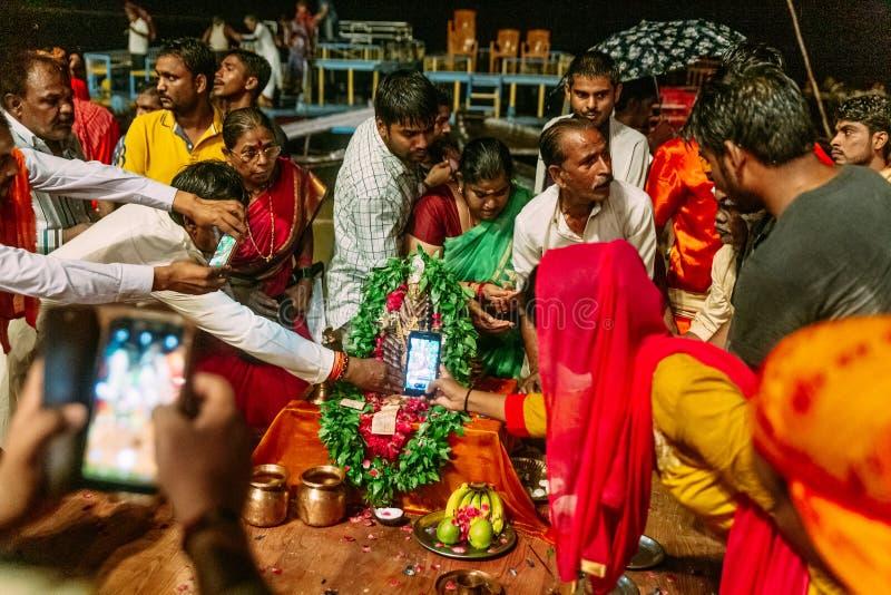Indian people got bless in Varanasi Ganga Aarti at holy Dasaswamedh Ghat, near Kashi Vishwanath Temple while raining at night. Indian people got bless in royalty free stock photo
