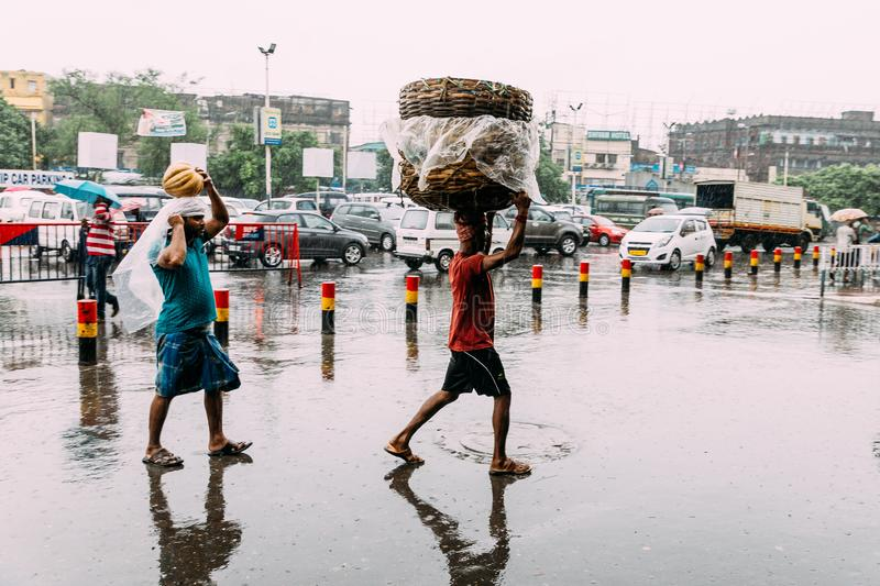 Indian people walking in the rain with carry goods to the train near the area of Howrah Junction railway station stock photography