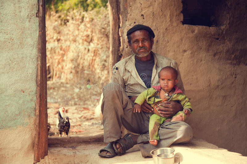 Indian poor father and son. Sitting on ground and he is holding his son royalty free stock photos