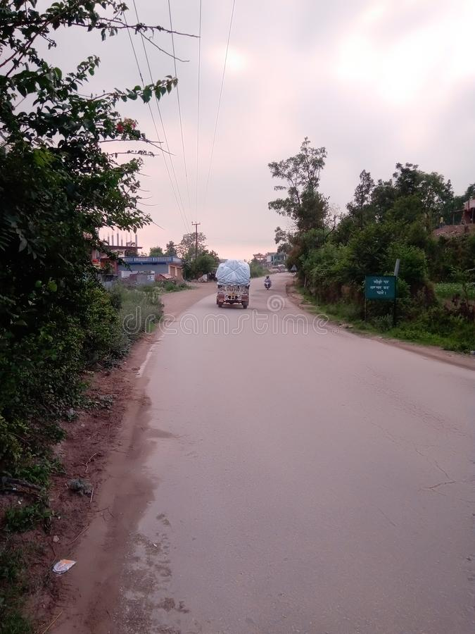 Indian road and going to loaded jeep on road stock photo