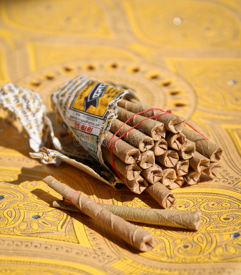 Indian rolled-up cigarettes. A bunch of rolled-up Indian cigarettes called beedi on an oriental yellow background stock photos