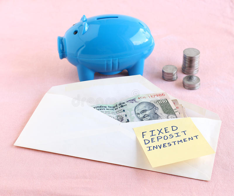 Indian Rupees and Fixed Deposit Concept. Fixed deposit investment concept indicated by the handwritten text on a paper on an envelope with Indian rupees stock images