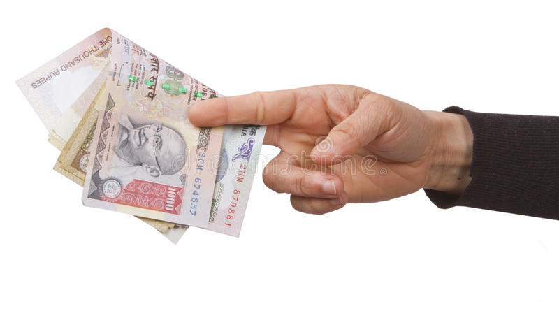Indian rupees. Holding and giving Indian rupees to someone from purse royalty free stock image
