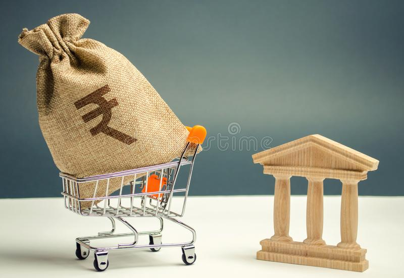 Indian rupees in a supermarket cart and a bank or government building. Business and finance concept. Investing in a bank. Deposit stock image