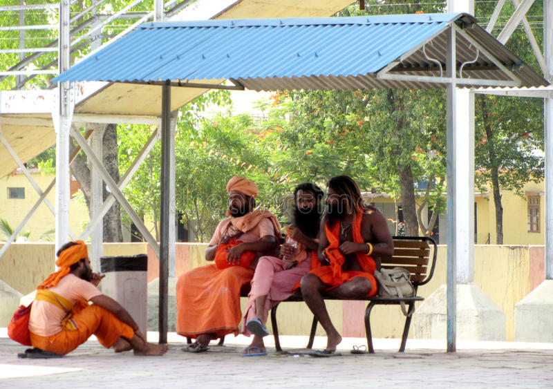 Indian sadhus sitting on a railway station. Four of indian sadhus or holy-men waiting on a railway station for the train to come royalty free stock images