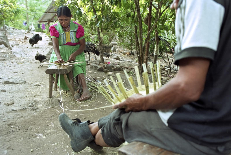 Indian seniors braiding wicker baskets for sale. Guatemala, department of Chiquimula, village, municipality Jocotan: elderly Indian woman and man sitting in stock images