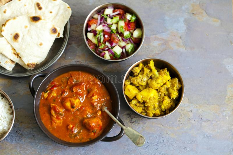 Indian sharing meal. Indian meal with chicken tikka masala, aloo gobi, raita, flatbreads and salad stock images