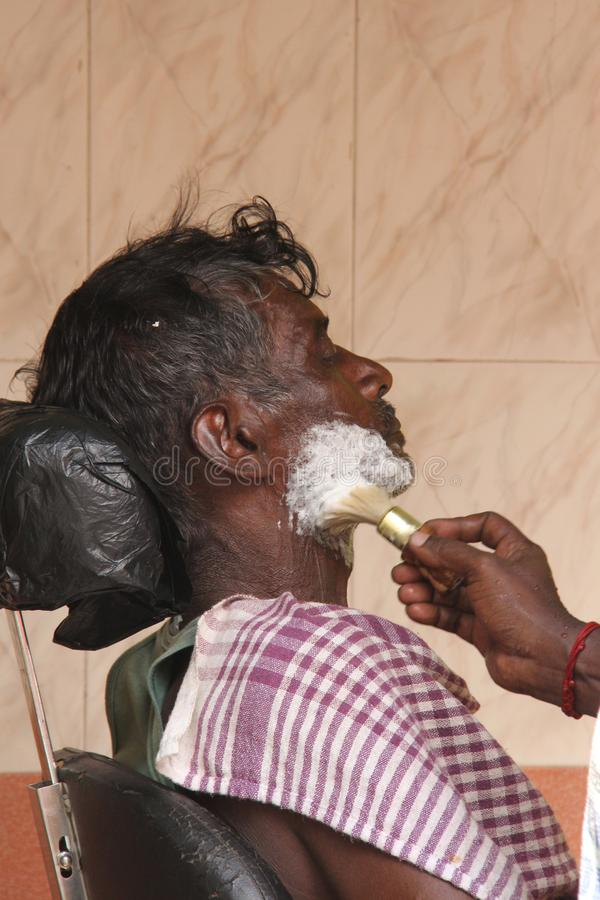 Having a shave at the barbers. An indian sits back while his face is lathered by the barber for an old fashioned shave stock photos