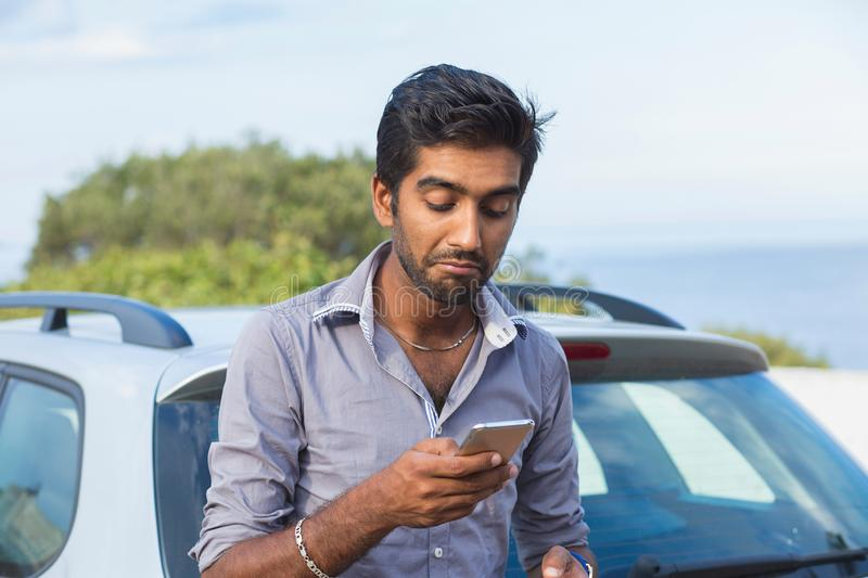Indian skeptical frustrated surprised sad man checking looking at phone texting. Calling dealership after a car breakdown royalty free stock image