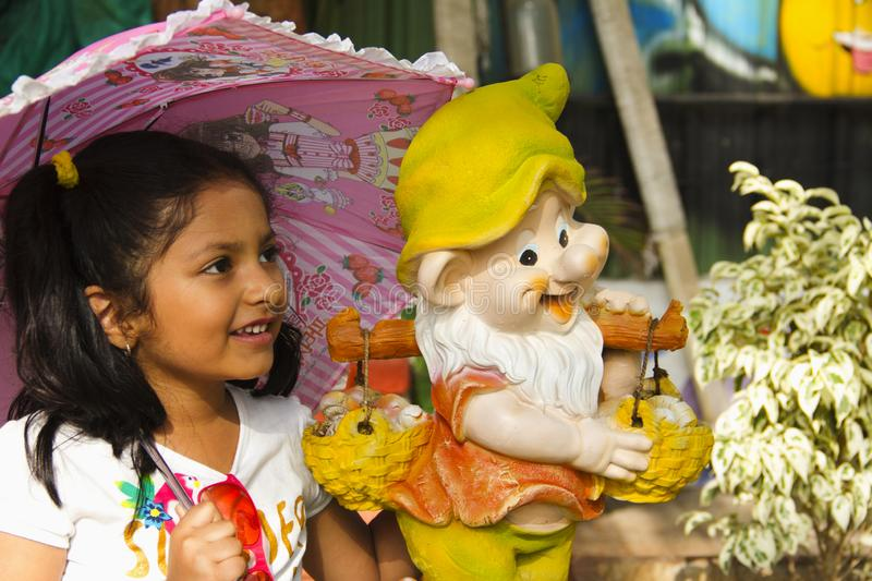 Indian small girl with cartoon statue smiling while holding pink umbrella inside garden, Pune royalty free stock photos