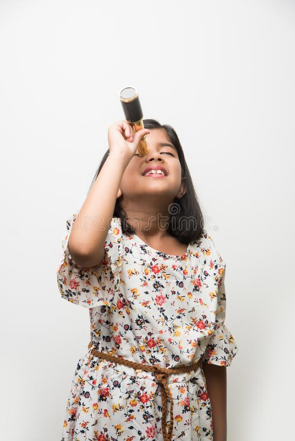 Indian small girl using telescope and studying space science stock image